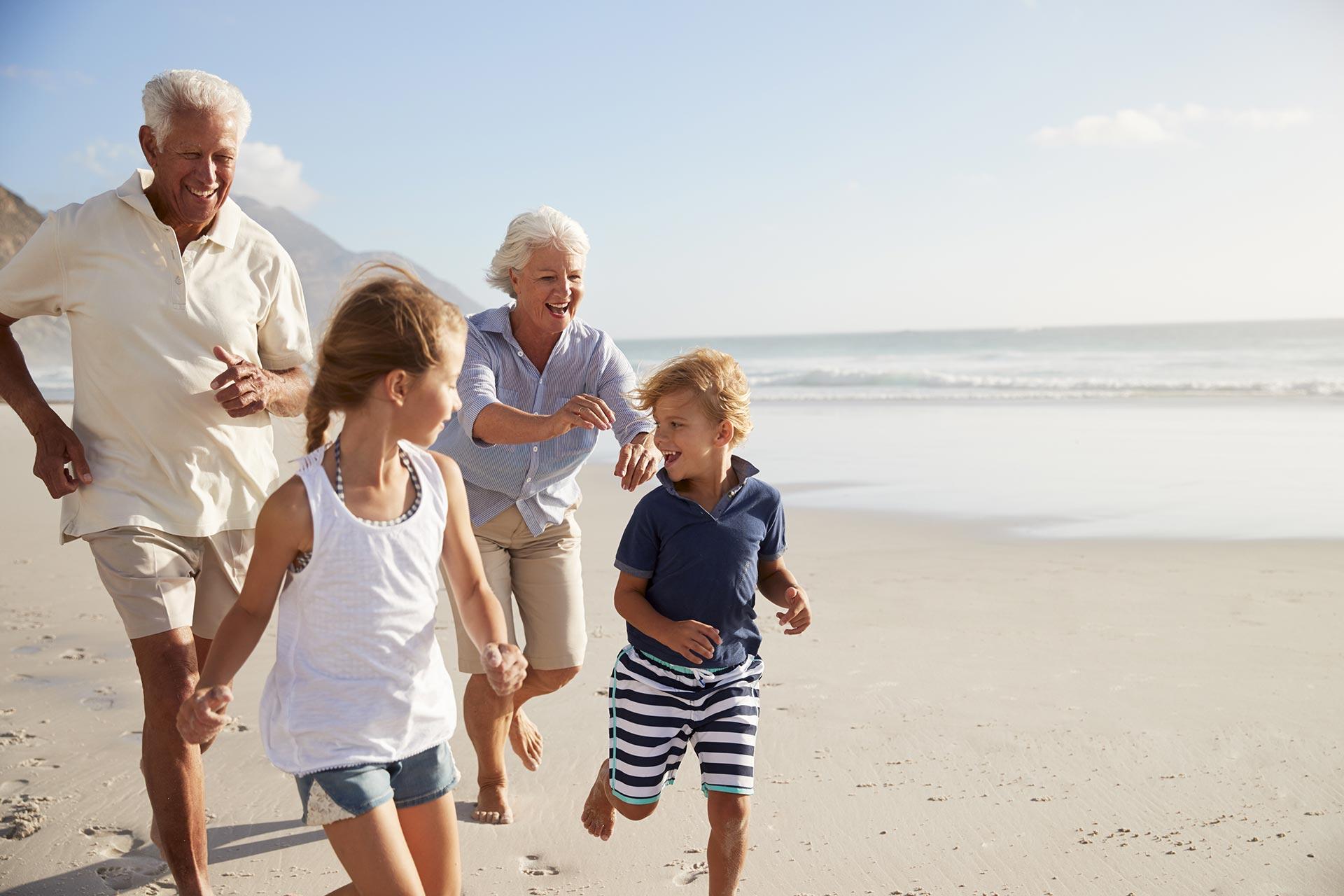 grandparents and kids running on beach